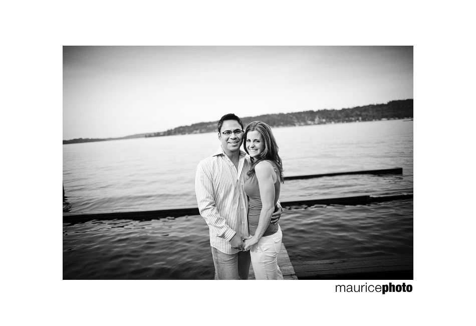 Picture of a couple posing on a dock near the lake.