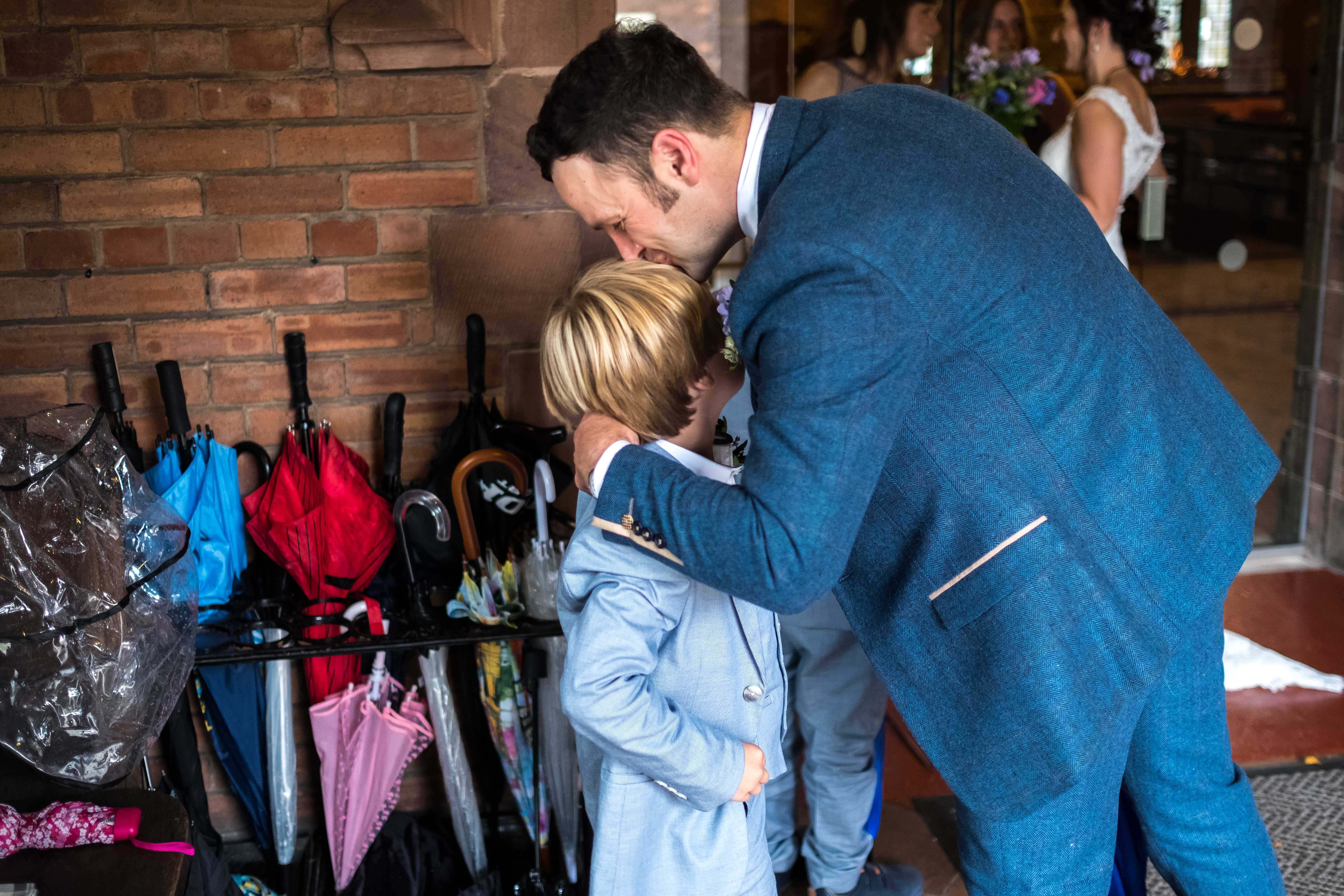 Groom hugging a young family member following the wedding ceremony at All Saints church in Chester.