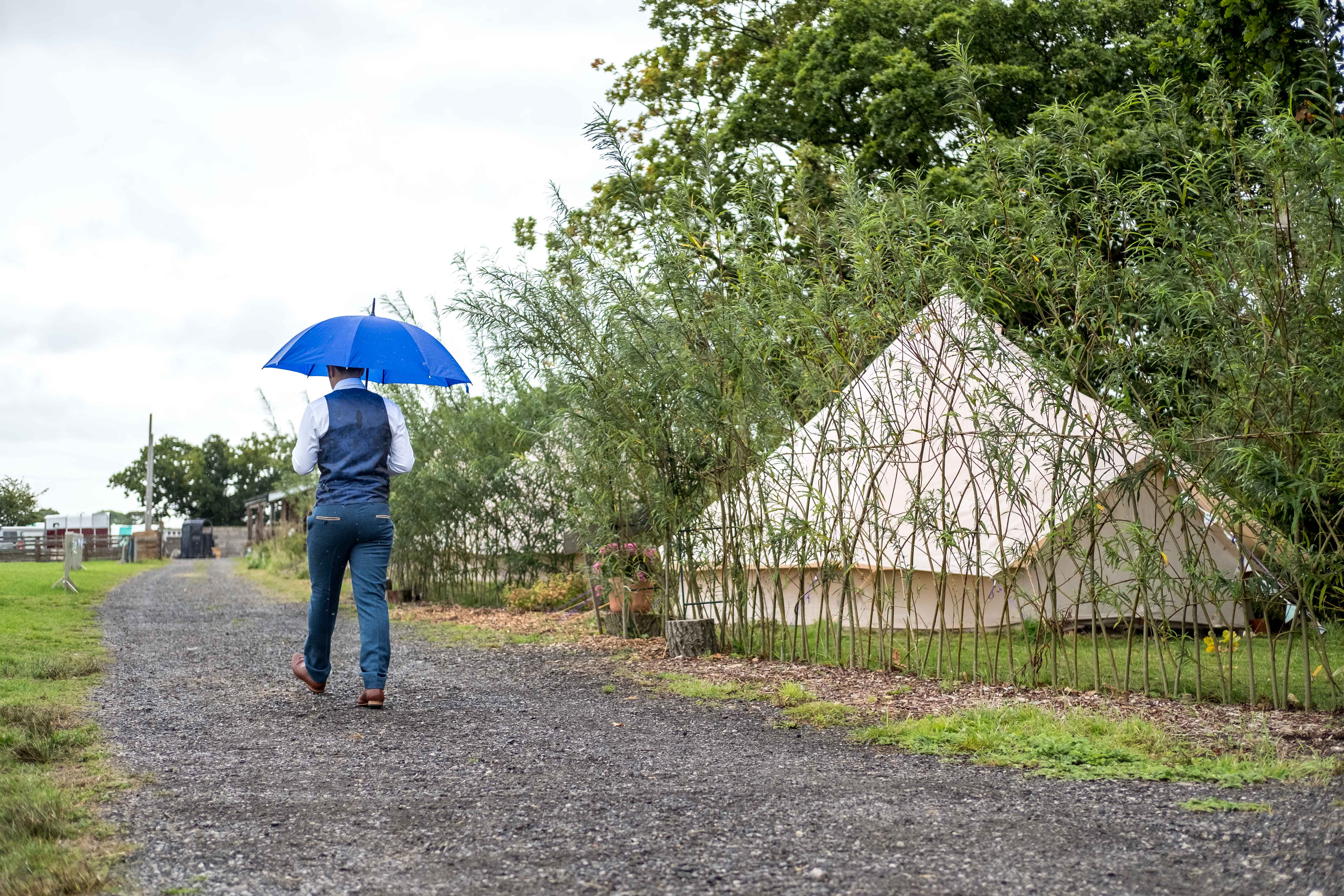 Chester wedding Photographer - Groom walking with an umbrella in the rain, walking past a teepee at his wedding in King Acres