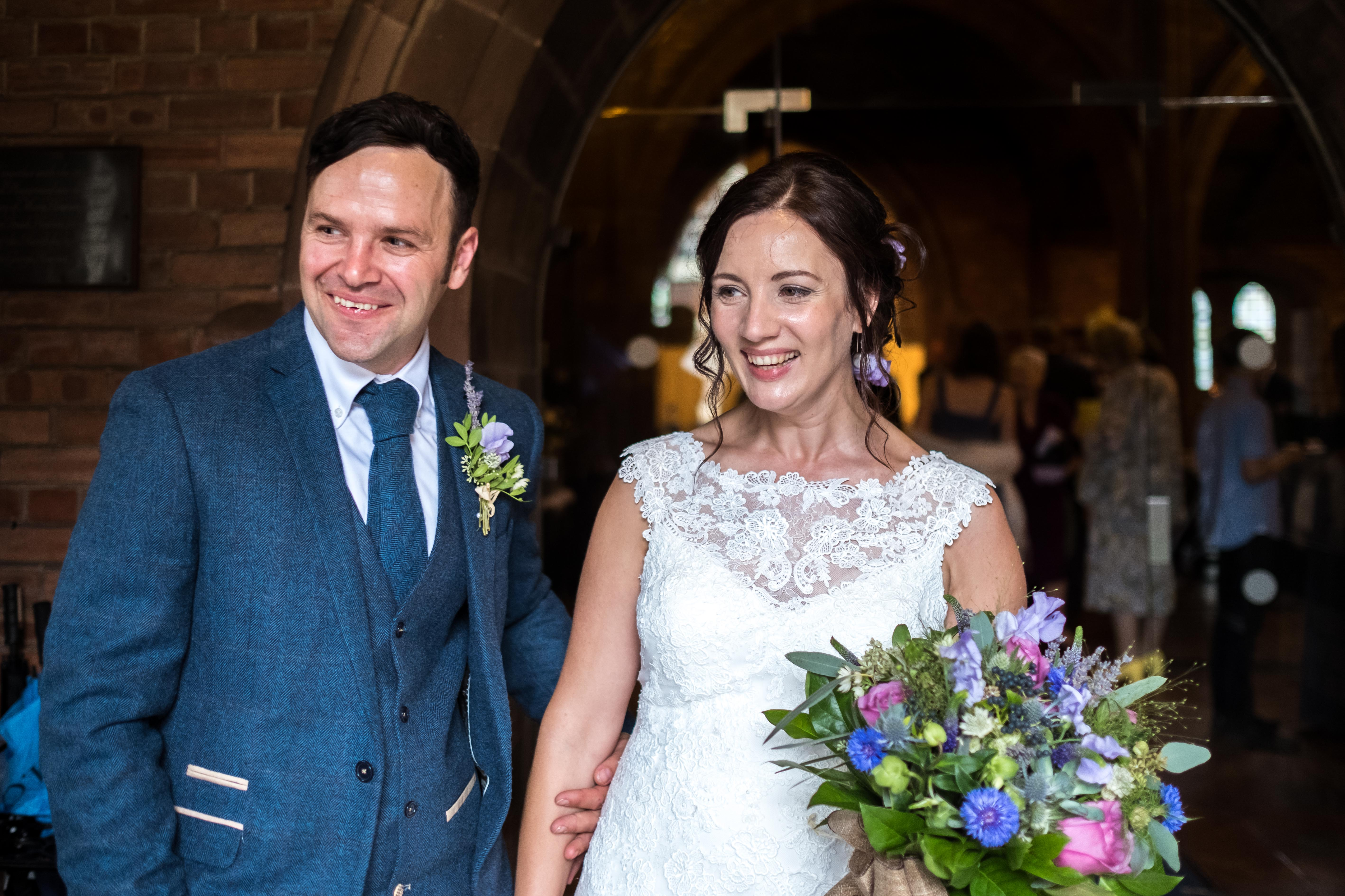 Bride and groom just married standing in the main entrance of All saints church in Chester.