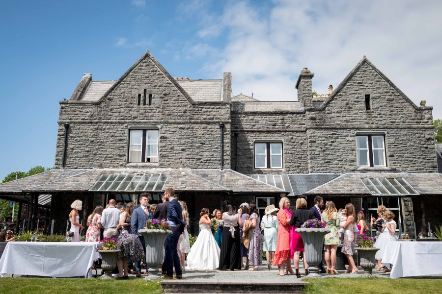 The view from the terrace at a Bron Eifion Wedding. With guests congratulating the happy bride and groom and having drinks.