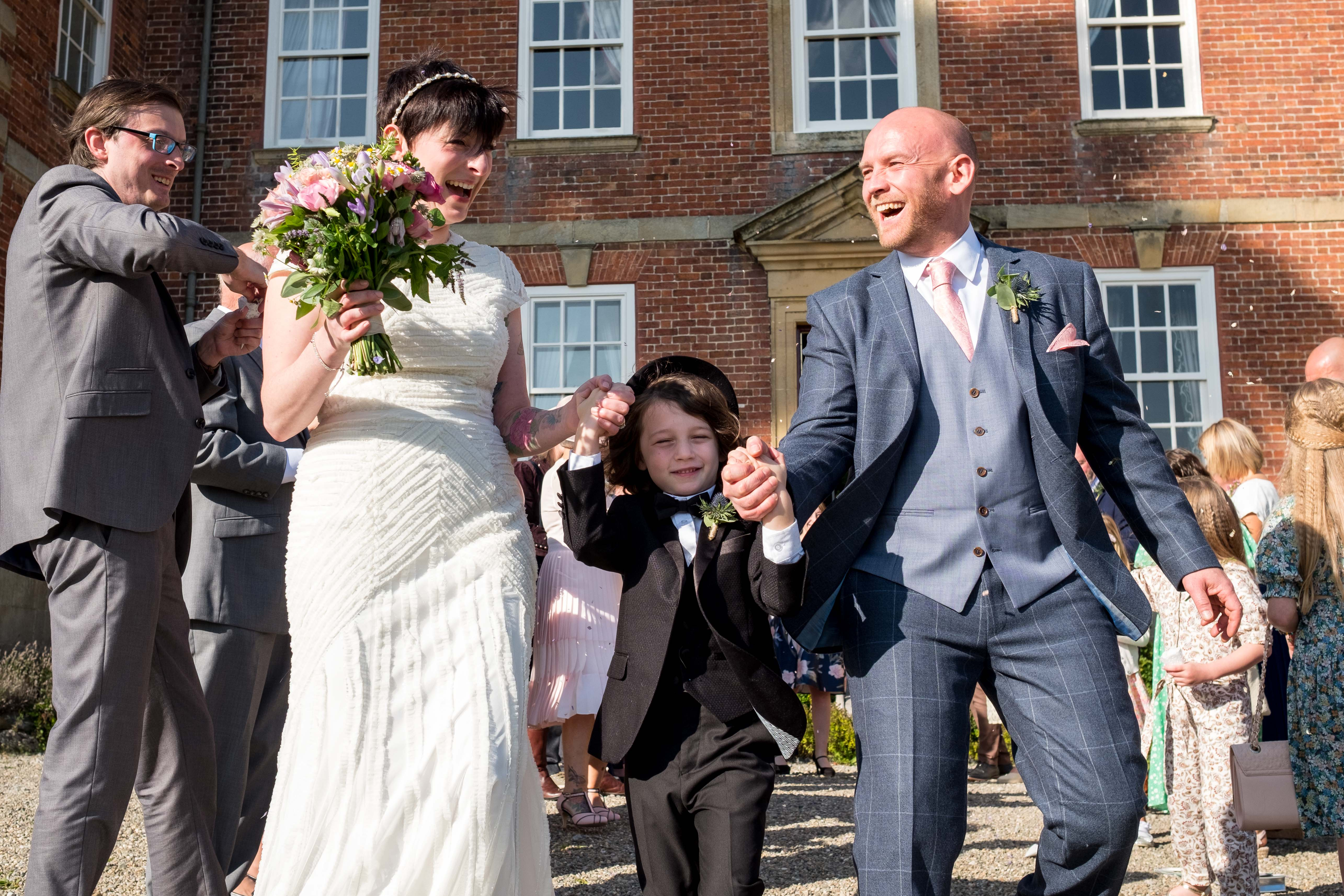 Llangollen wedding at Trevor Hall confettie being thrown over the bride and groom.