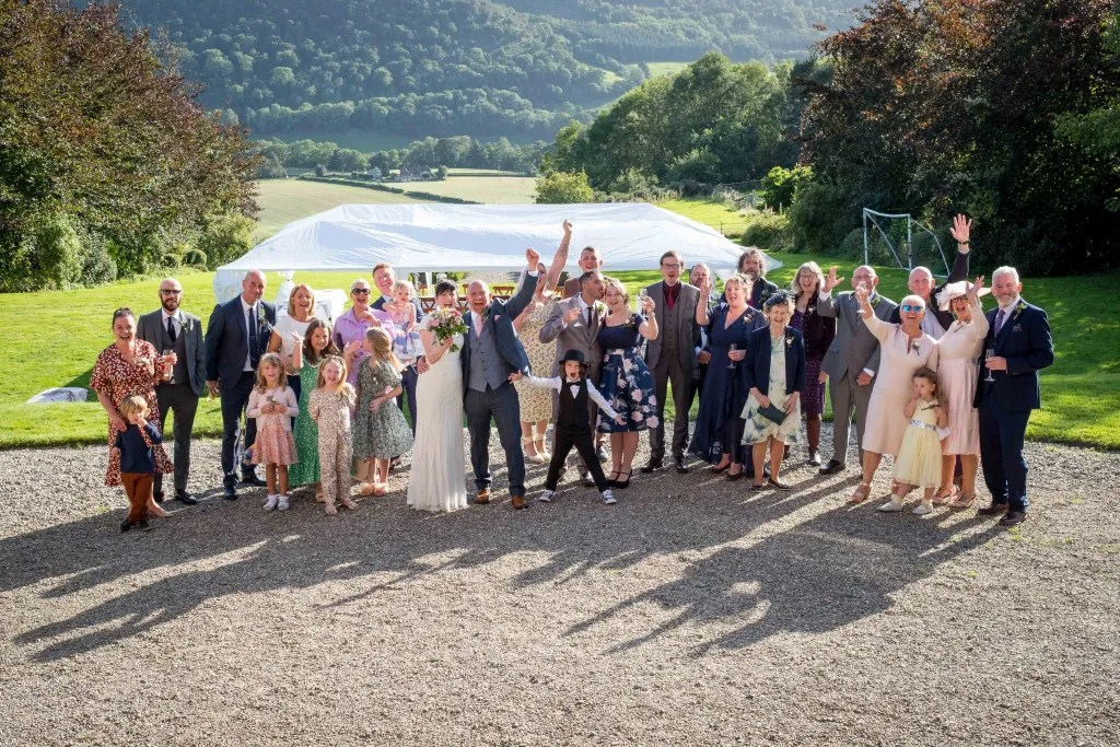 The whole wedding party outside the front at Rachel and Pauls Trevor Hall wedding in Llangollen.