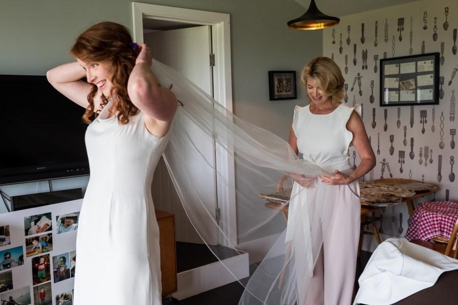 Mum helping her daughter put a veil on at Llyn Peninsula wedding.