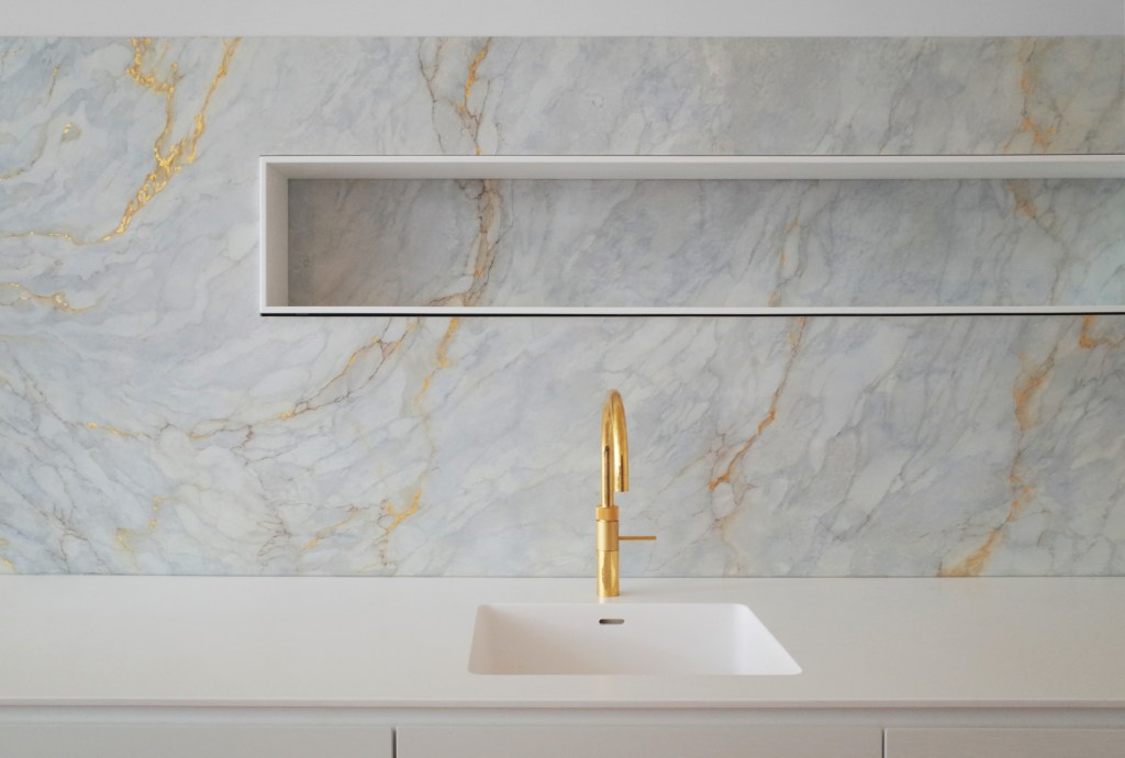 Marble custom architectural kitchen design with gold limited edition Cooker and hi-macs counter