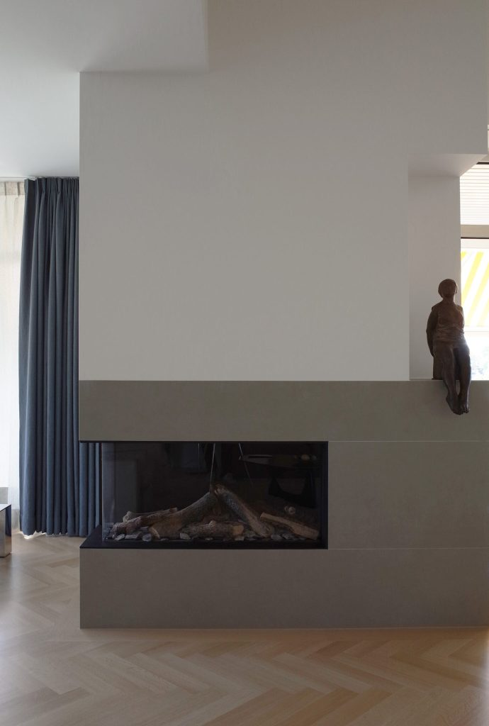 Fireplace in penthouse design by architect Maurice van Bakel with herringbone wooden floors