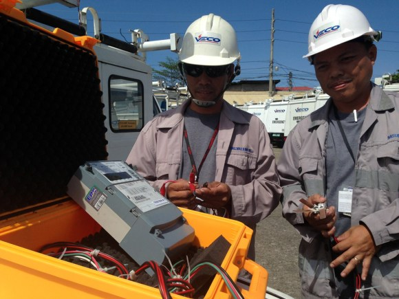 Technician Niceporo Salvaleon, Jr. and meter engineer Alvin Basubas shows the power meter tester that they built for about P25,000 to do the job previously done by a machine that costs about P1.9 million.