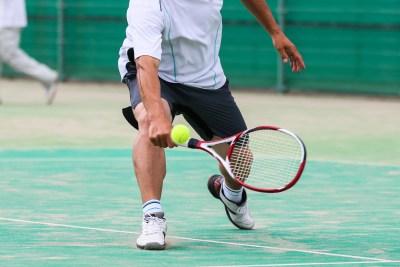 テニスでバックハンドをする男性