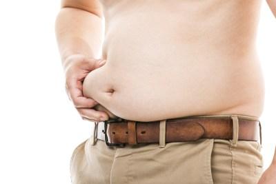 お腹の贅肉をつまむ太った男性