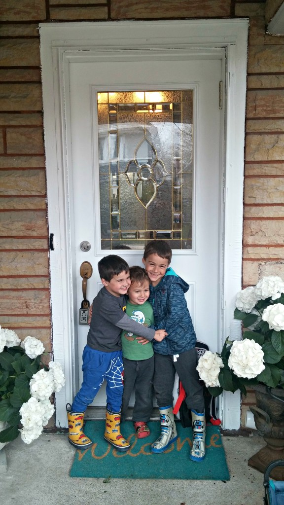 breath three boys in front of house