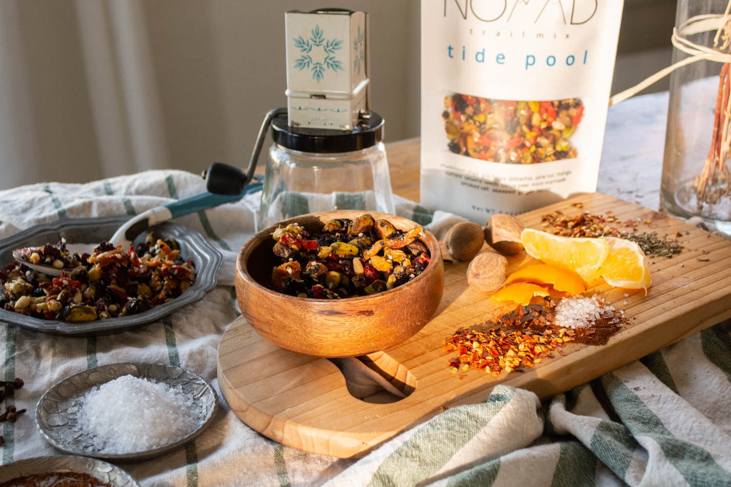 Nomad trail mix with raw ingredients spread out on table arranged in sunlight. food photography