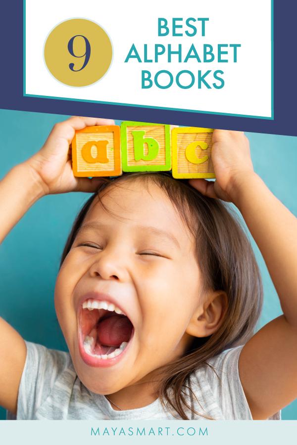 Little girl holding ABC blocks over her head