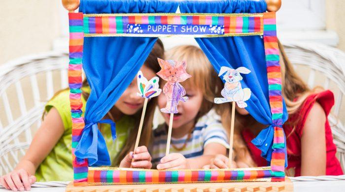 Three children hold up puppet sticks behind a miniature stage