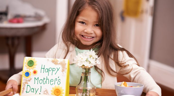 little girl holding breakfast tray for Mother's Day