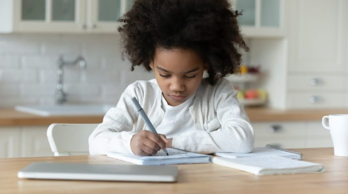 Little girl writing letter at kitchen table
