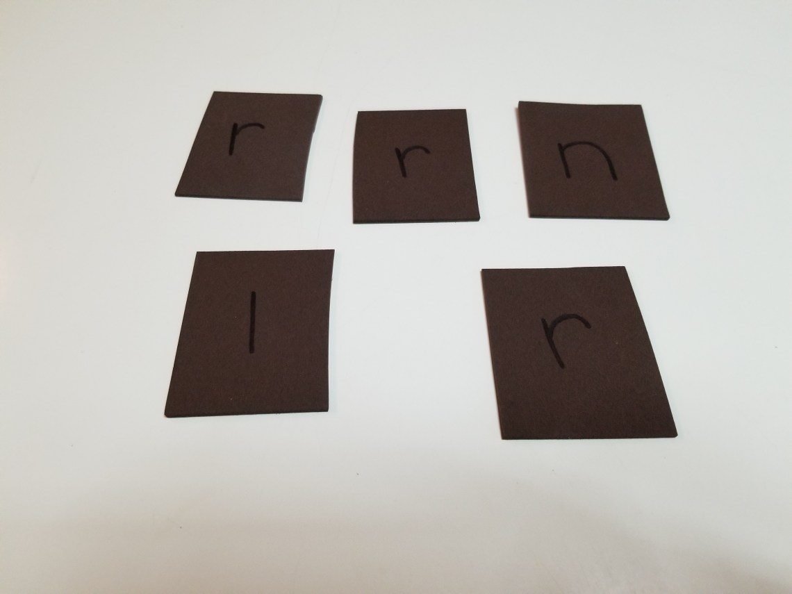 dark brown construction paper cut into squares with letters drawn on each square