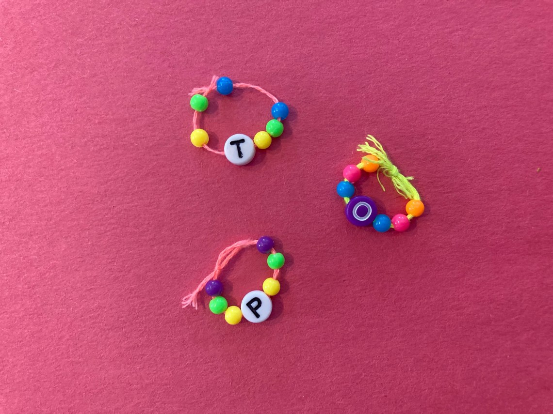 three rings made out of string and beads