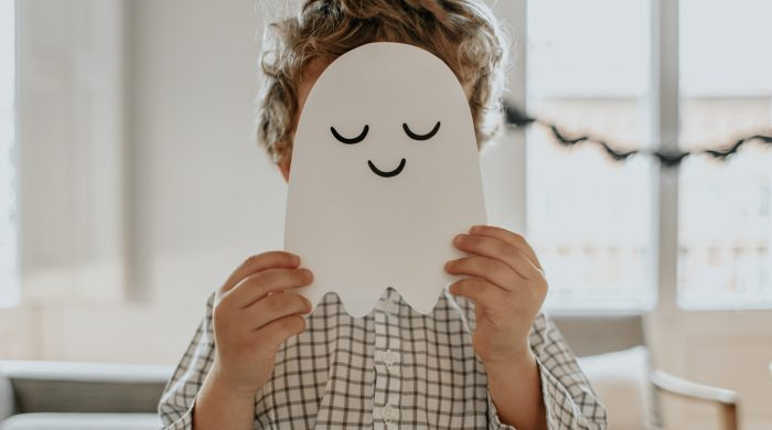 Little boy holding up a paper ghost