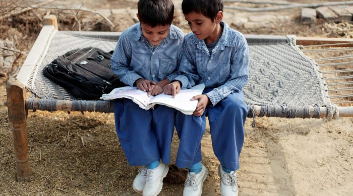 two little boys sitting side by side reading