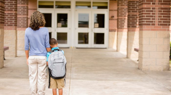 Mom and son look at school building