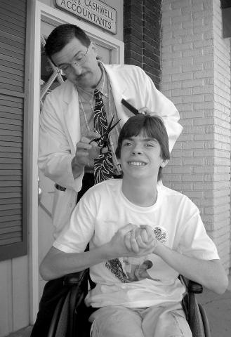 Floyd trimming up Kyle's hair on the streets of Mayberry Days.
