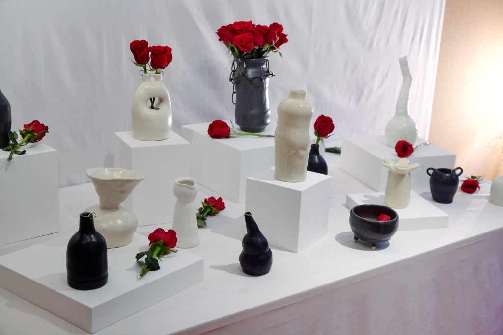 A white-clothed table with multiple ceramics in black and white scattered about with red roses.