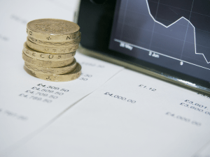 Image of stack of pound coins in front of computer screen showing a downwards trend on a graph