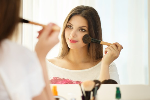 Beauty woman applying makeup. Beautiful girl looking in the mirror and applying cosmetic with a big brush. Girl gets blush on the cheekbones. Powder, rouge ; Shutterstock ID 205957348