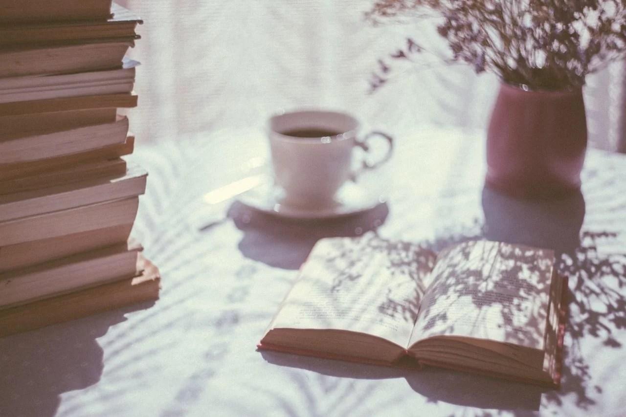 imagen romántica, libro abierto con taza de café florero y pila de libros