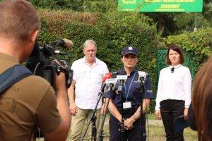 Umundurowana policjantka, w tle stoi mężczyzna z kobietą
