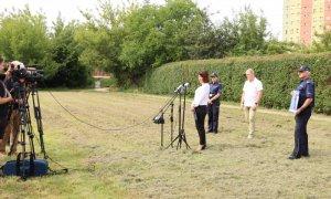 Kobieta stoi przed mikrofonem, w tle dwóch policjantów i mężczyzna