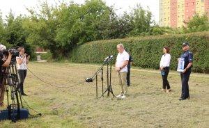 Mężczyzna stoi przed mikrofonem, w tle dwóch policjantów i kobieta