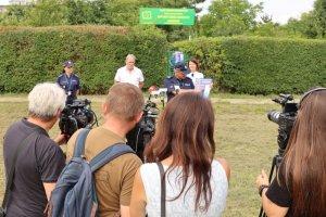 Dziennikarze stoją naprzeciw dwóch policjantów, kobiety i mężczyzny