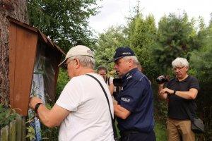Mężczyzna i policjant przypinają plakat na tablicę informacyjną