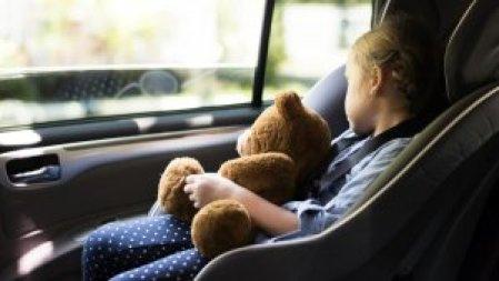 Fotografia kolorowa: wnętrze pojazdu, w foteliku samochodowym śpi dziecko a na kolanach trzyma misia.