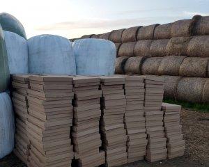 pudła kartonowe 265 ustawione na polu za belami sianokiszonki