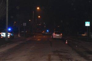 ulica nocą przejście dla pieszych za którym stoi samochód osobowy. Przejście zabezpiecza Policja