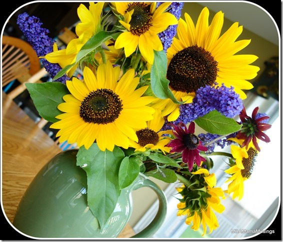 Sunflowers, butterfly bush, and coneflower arrangement in a green pitcher