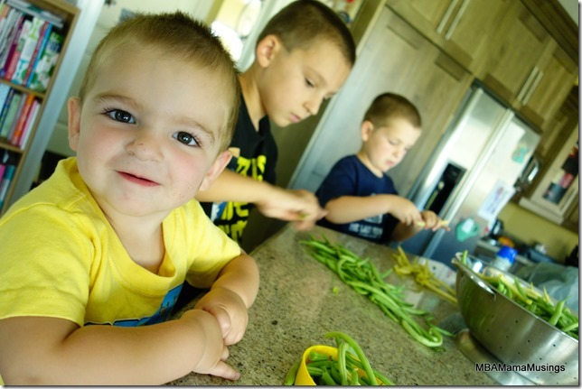 Three boys snapping green beans sitting at a counter