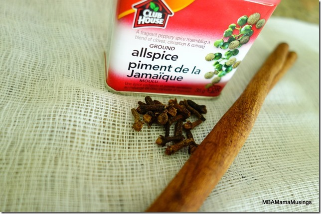 Can of ground allspice, loose cloves, and a stick of cinnamon sitting on cheesecloth