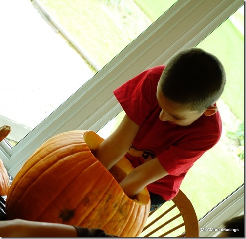 Boy Digging Into Pumpkin with Both Hands