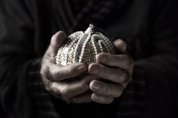 closeup of an old caucasian man holding an elegant christmas bal