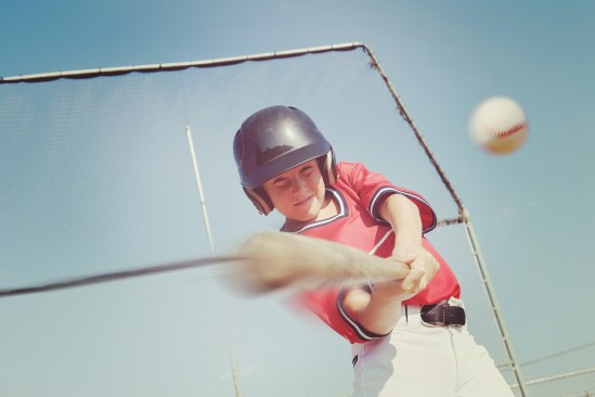 Young baseball player hitting the ball.  Vintage instagram effec