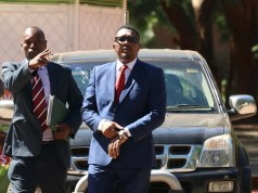 Former Minister of Foreign Affairs Walter Mzembi is escorted by a detective during his appearance at the Harare Magistrates Court in Harare