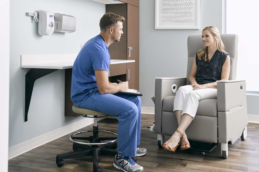 Patient talking to doctor in hospital chair