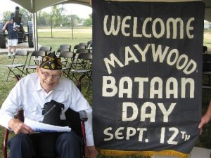 Phillip Burns, brother of William Burns (HQ), donates an original Bataan Day banner.