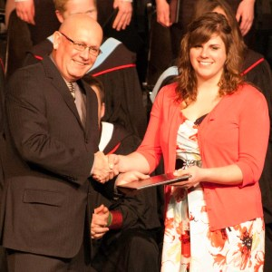 Bethany president Howie Wall congratulates Dynel Weber, winner of the 2nd-year academic award (for excellence in a creative project)