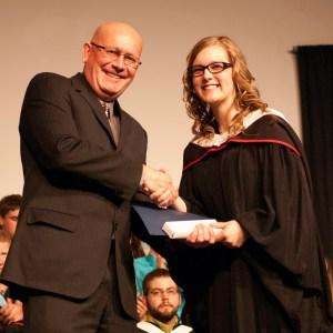 Bethany president Howie Wall congratulates Kaylee Buhler, winner of the Delta Epsilon Chi award