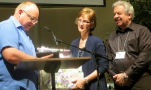 """Retiring BCMB director of administration Marilyn Hiebert receives a """"grandma"""" gift from moderator Ron van Akker as husband Rudy looks on. And, oh - something in an envelope."""