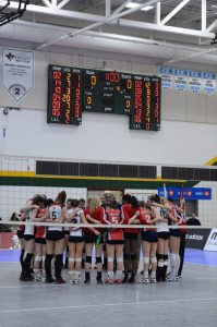 CBC Bearcats pray with an opposing team from Quebec after their volleyball game. Photo: Brin Dyer - Lakeland College